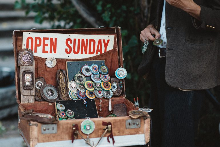 man selling trinkets from a suitcase