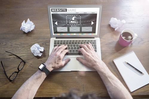 Centered laptop and a person sitting behind it with just his hands visible, while there are thrown pieces of paper around him