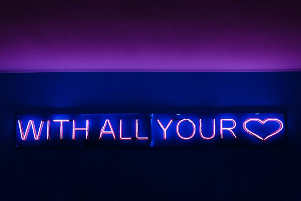 neon sign that says with all your heart