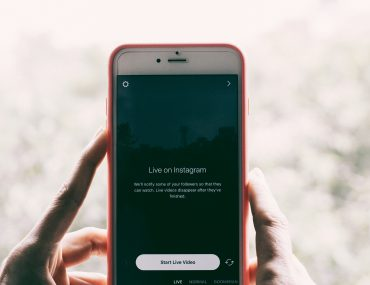 person holding phone with live on instagram screen