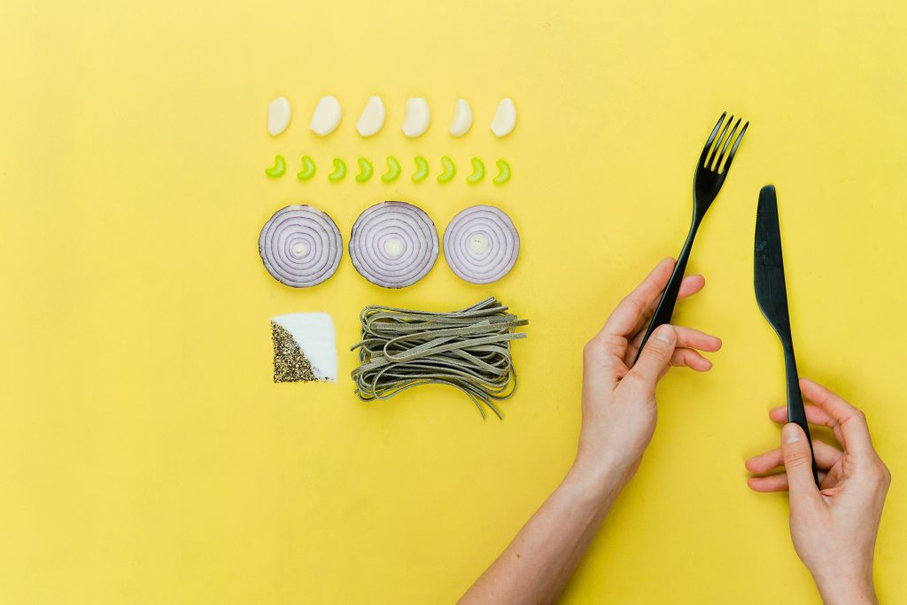 a woman's hands holding a fork and a knife with many ingredients on a yellow background which indicates product descriptions