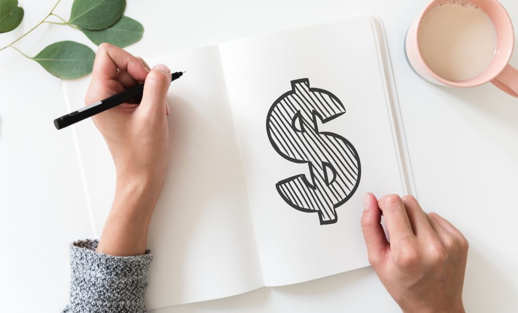 woman's hand drawing a dollar sign