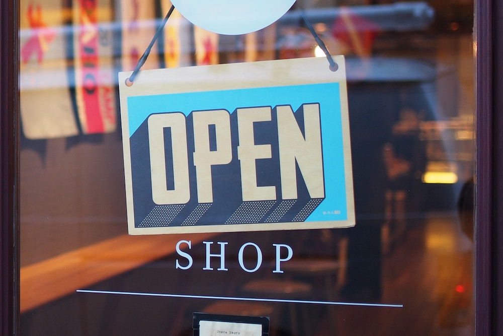shop with a table that says Open, which represents Amazon's brick and mortar dreams