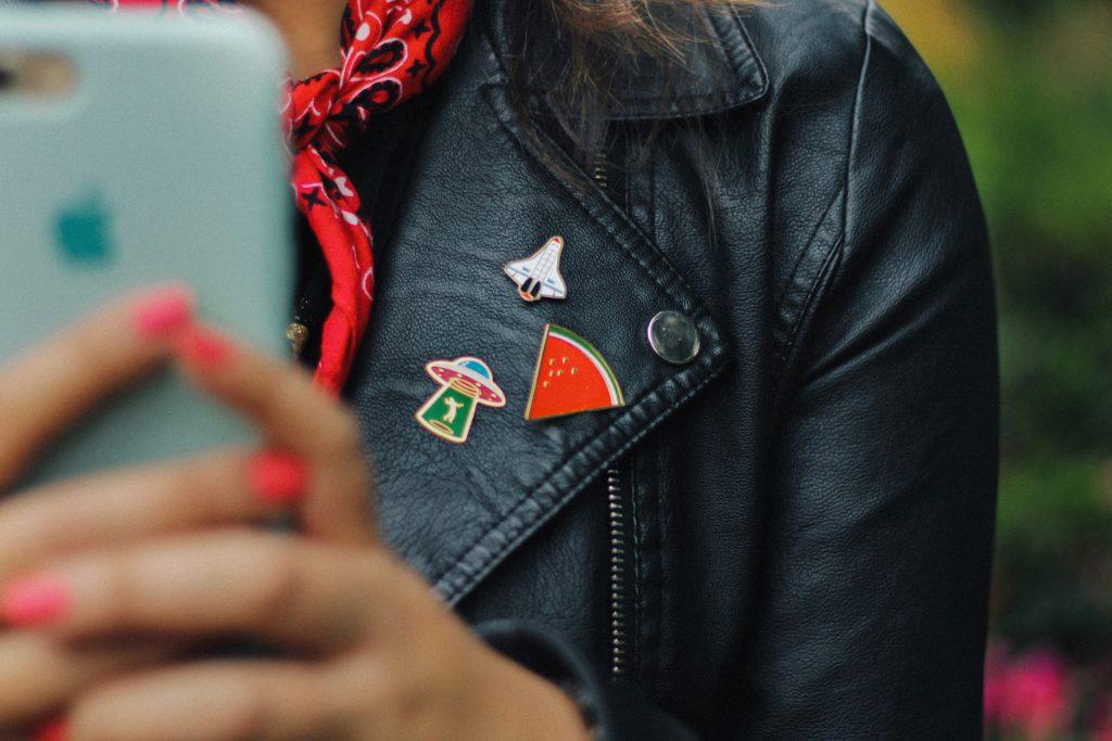 girl wearing enamel pins on her leather jacket